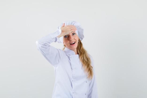 Chef mujer sosteniendo la mano en la frente en uniforme blanco y mirando alegre.
