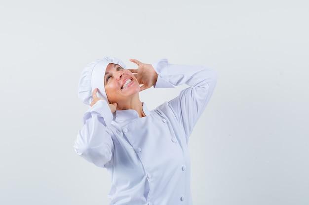 Chef mujer en uniforme blanco fingiendo usar auriculares y mirando encantada