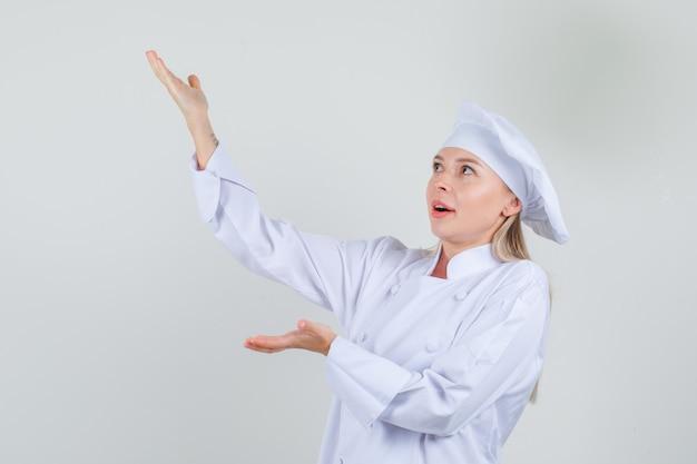 Chef mujer en uniforme blanco gesticulando como sosteniendo algo