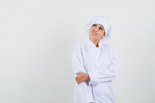Chef mujer en uniforme blanco mirando hacia arriba y mirando pensativo