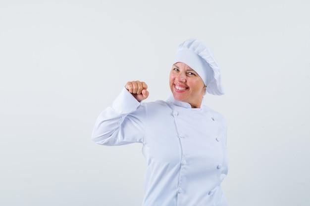 Chef mujer en uniforme blanco mostrando gesto ganador y mirando feliz