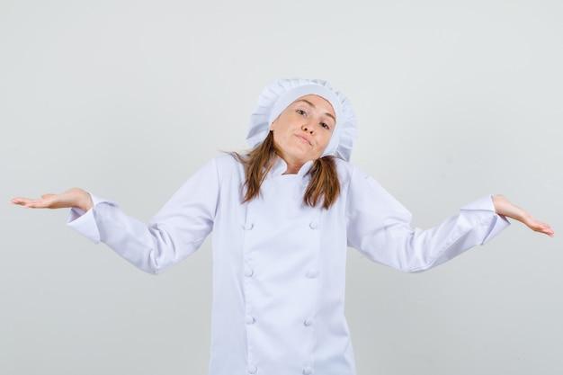 Chef mujer en uniforme blanco mostrando gesto de impotencia y mirando confundido