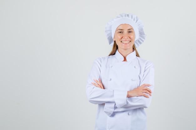 Chef mujer en uniforme blanco de pie con los brazos cruzados y mirando alegre