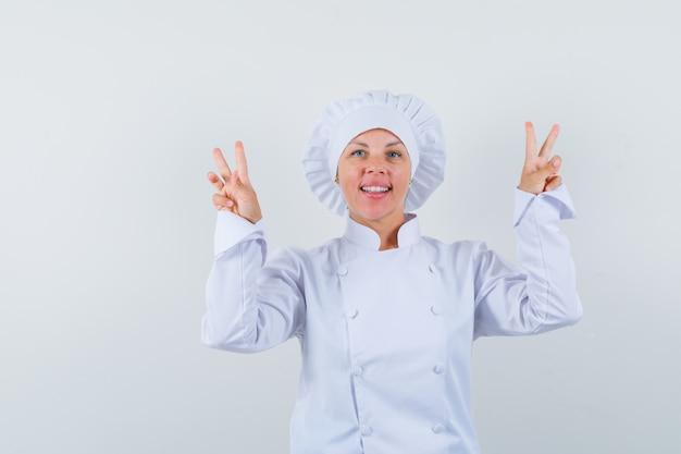 Chef mujer en uniforme blanco que muestra el signo v y parece seguro