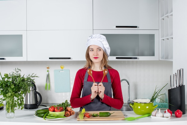 Chef mujer vista frontal en delantal sosteniendo cucharas