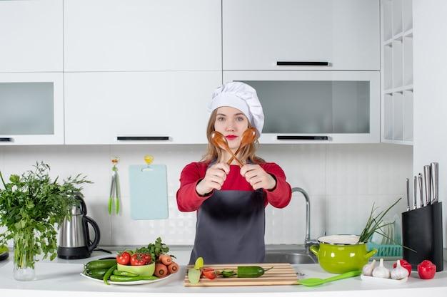 Chef mujer vista frontal en sombrero de cocinero sosteniendo cucharas cruzadas