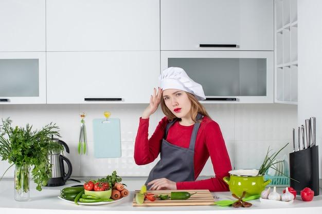 Chef mujer vista frontal en sombrero de cocinero sosteniendo su cabeza con dolor