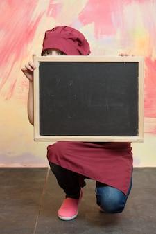 Chef niña o niño cocinero con sombrero rojo sobre fondo de colores detrás de la placa, espacio de copia, cocina y comida