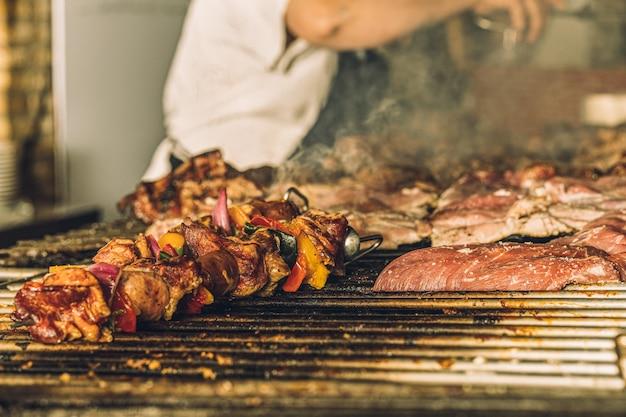 Chef no reconocido vistiendo un delantal preparando filetes y brochetas de carne en la parrilla de un restaurante.