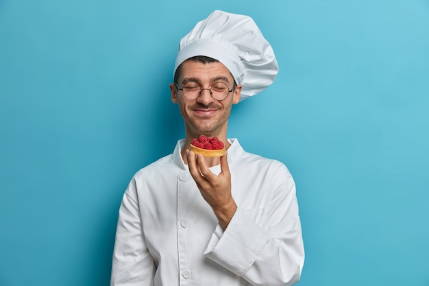 El chef de panadería huele pasteles recién horneados hechos a mano decorados con frambuesa, trabaja en la pastelería, cierra los ojos con placer
