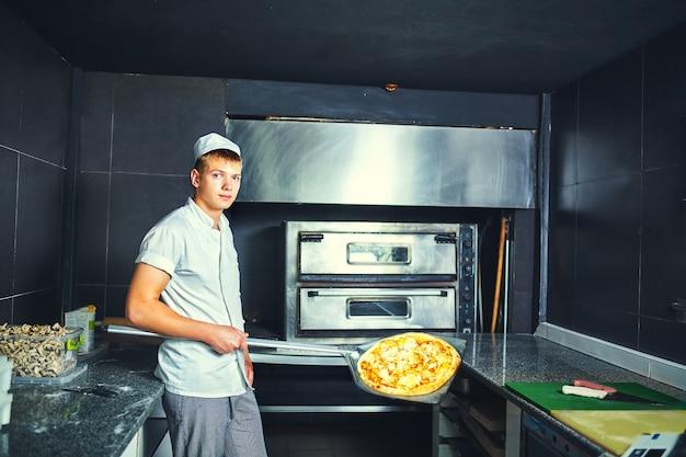 Chef panadero cocinero en uniforme negro poniendo pizza en el horno con pala en la cocina del restaurante.