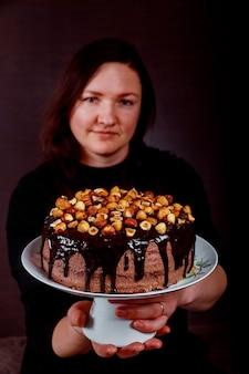 Chef pastelero feliz que muestra su pastel casero en su mano