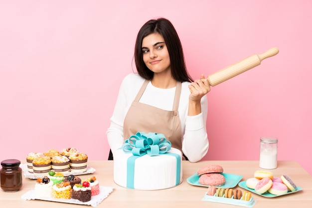 Chef pastelero con un gran pastel en una mesa sobre pared rosa