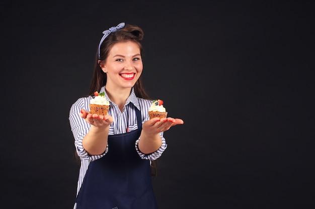 Chef pastelero con kopkeykami en manos de sonrisas a la cámara en el estudio sobre un fondo negro