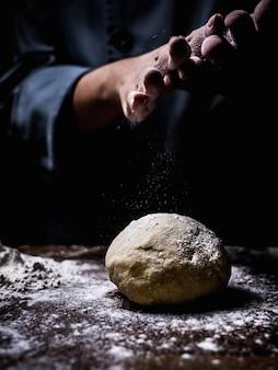 Chef pastelero mano espolvorear harina blanca sobre masa cruda en la mesa de la cocina.