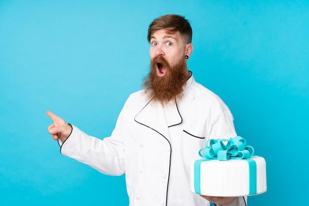 Chef pastelero pelirrojo con barba larga sosteniendo un gran pastel sobre pared azul aislado sorprendido y apuntando con el dedo a un lado