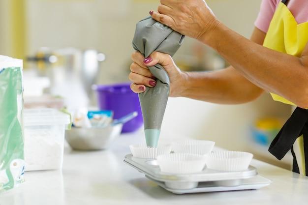 Chef pastelero profesional mujer extiende masa de chocolate en una fuente para horno