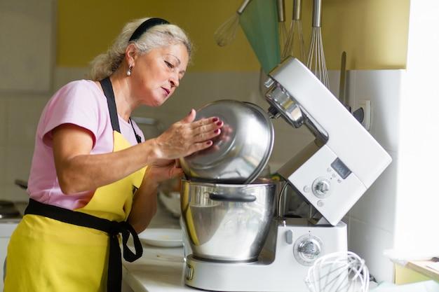 Chef pastelero profesional mujer preparando un postre. agrega ingredientes y mezcla la masa en una batidora