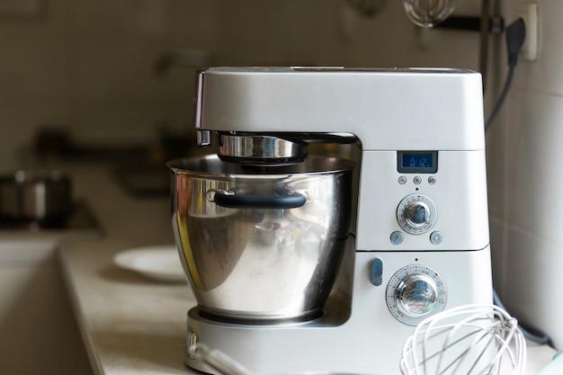 Chef pastelero profesional preparando un postre. agrega ingredientes y mezcla la masa en una batidora