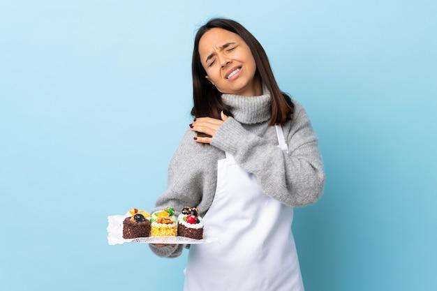 Chef pastelero sosteniendo un gran pastel en azul aislado que sufre de dolor en el hombro por haber hecho un esfuerzo
