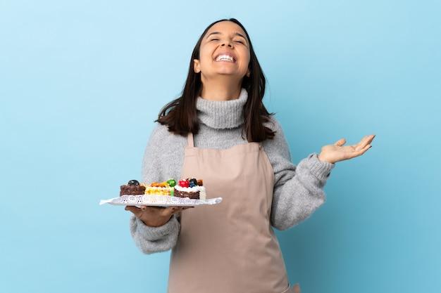 Chef pastelero sosteniendo un gran pastel en azul aislado sonriendo mucho