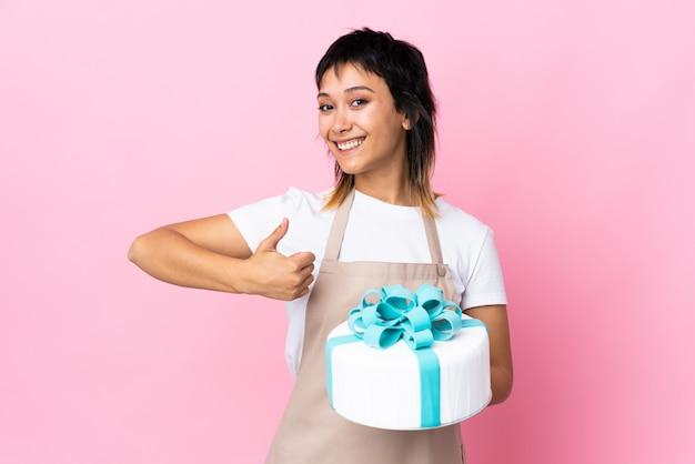 Chef pastelero sosteniendo un gran pastel sobre espacio rosa aislado dando un gesto de aprobación