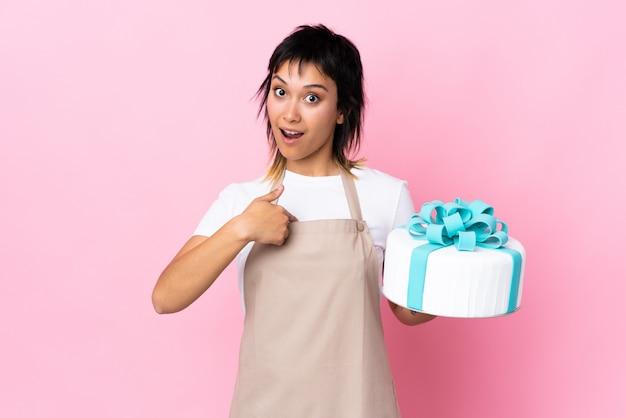 Chef pastelero sosteniendo un gran pastel sobre espacio rosa aislado con expresión facial sorpresa