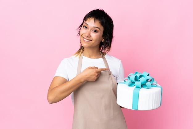 Chef pastelero sosteniendo un gran pastel sobre pared aislada