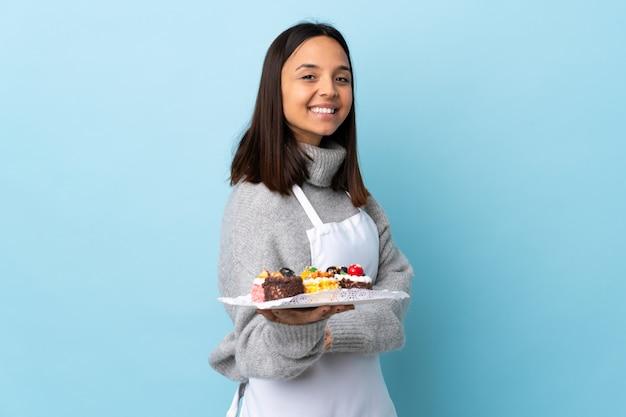 Chef pastelero sosteniendo un gran pastel sobre pared azul aislado con los brazos cruzados y mirando hacia adelante