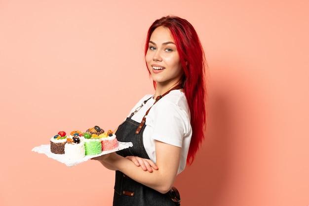 Chef pastelero sosteniendo un muffins aislado en la pared rosa con los brazos cruzados y mirando hacia adelante