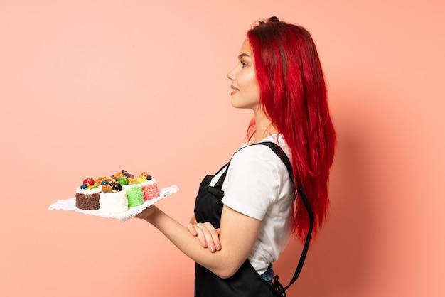 Chef pastelero sosteniendo un muffins aislado en pared rosa en posición lateral