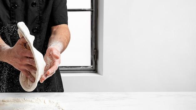 Chef de pizza haciendo masa de pizza con espacio de copia