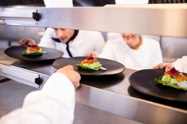 Chef con plato de aperitivo listo en la estación de pedidos