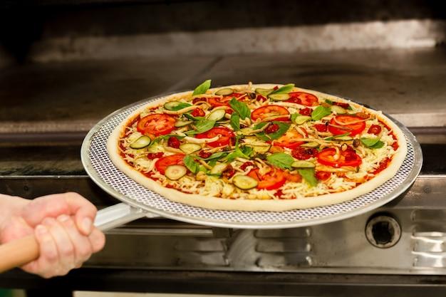 Chef poner pizza en el horno con equipo de pala de pizza.