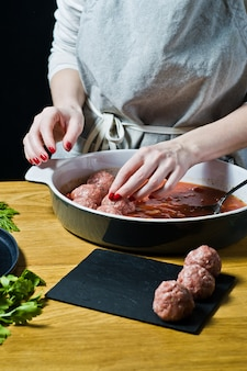 Chef prepara albóndigas suecas de carne picada cruda, salsa de tomate revuelva.
