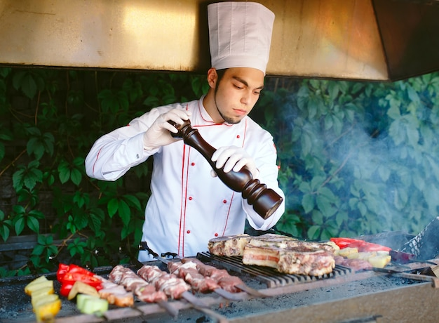 El chef prepara carne en la barbacoa.