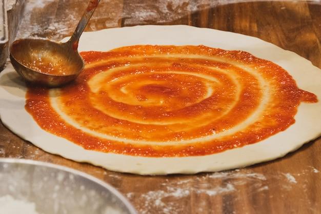 Chef prepara deliciosa pizza en la cocina.
