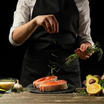 El chef prepara pescado fresco de salmón, trucha recién salada, salpicado de hojas de romero con ingredientes.