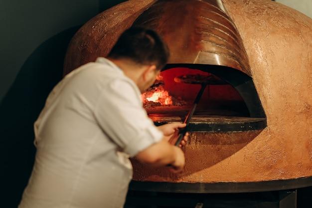 El chef prepara la pizza en un horno de leña. cocinar pizza. el cocinero mete la pizza en el horno. deliciosa pizza caliente del horno.
