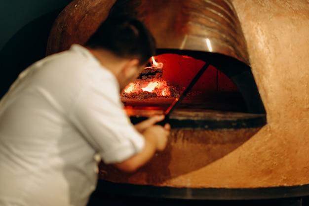 El chef prepara la pizza en un horno de leña. cocinar pizza. el cocinero mete la pizza en el horno.