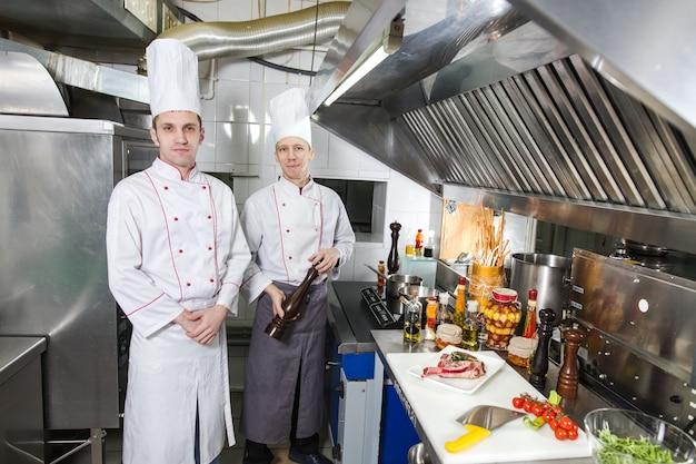 El chef prepara un plato en la cocina de restoran.