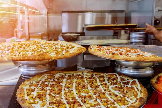 Chef en la preparación de deliciosas pizzas en la cocina. pizza de estilo italiano en el mostrador antes de hornear.
