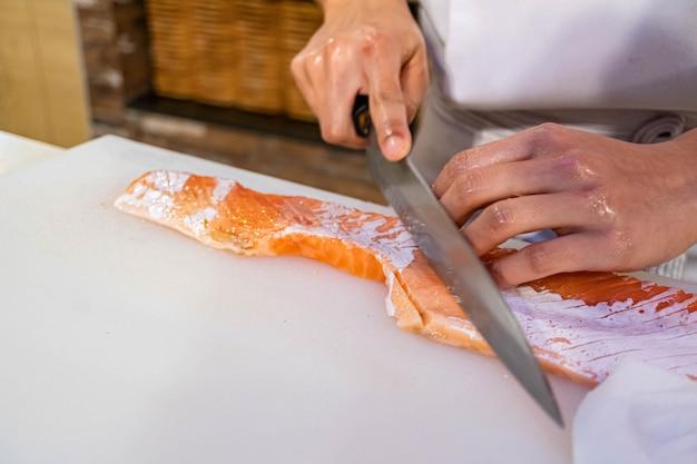 Chef preparando y cortando salmón fresco en restaurante japonés