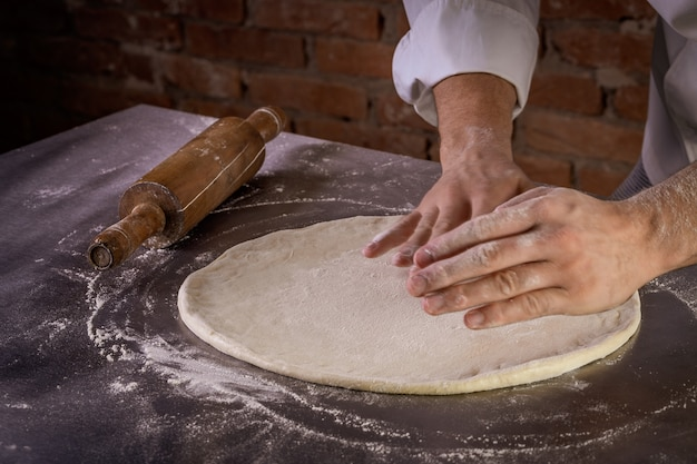 Chef preparando masa de pizza en la cocina