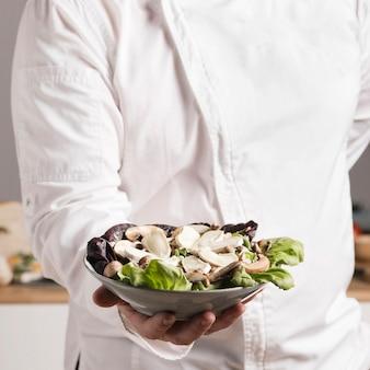 Chef de primer plano con plato de comida