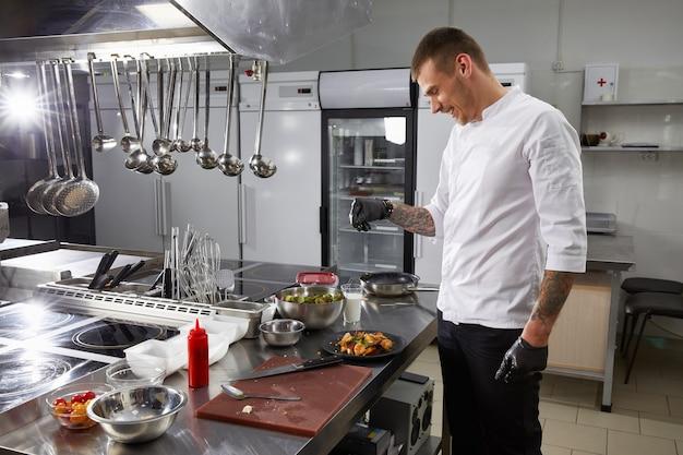 Chef profesional cocinando en la cocina moderna en el restaurante del hotel preparando ensalada de camarones