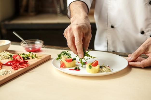 Chef profesional hombre maduro cocinando comida en el interior