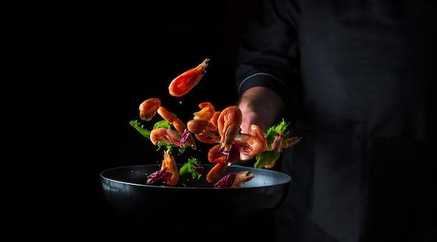 Chef profesional prepara camarones con hierbas. cocinar mariscos, comida vegetariana saludable y comida sobre un fondo oscuro. espacio publicitario gratuito