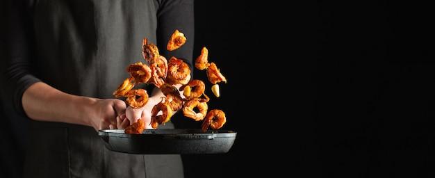 Chef profesional prepara camarones o langostinos
