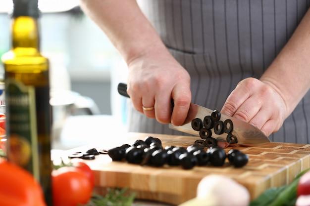 Chef profesional que corta el ingrediente de la aceituna negra